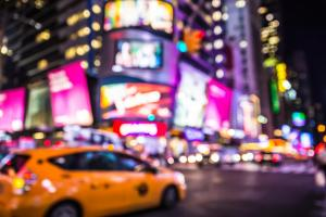 Defocused blur of Times Square in New York City with lights at n